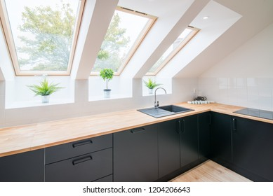Bright kitchen with slanted ceiling. Modern bright flat apartment in the attic. Kitchen with black kitchen cabinets