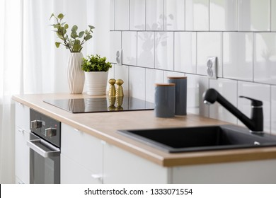 Bright kitchen with white tiles, wooden countertop and black sink
