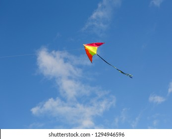 Bright kite against the blue sky. Sunny day. Sky clouds.