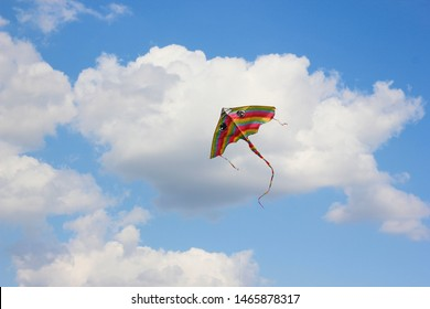 Bright kite flying in the clouds and blue sky in the background.
