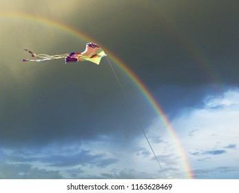 Bright kite in the form of a bird in the sky with a rainbow and dark clouds after the rain in summer.