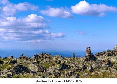 bright landscape of a high-altitude plateau with folded travelers pyramids cairns of stones under a blue sky with clouds