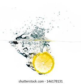 Bright lemon slice falling into water. Refreshing and healthy.