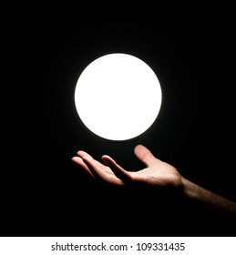Bright light ball over human hand isolated on black background