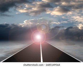 bright light at the end of a deserted road under a cloudy