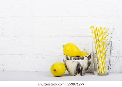 Bright light modern kitchen still life juicy lemons in a bowl and yellow marble cocktail tube high a glass against a white brick wall. The horizontal design