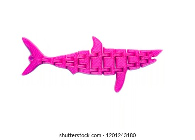 Bright light pink object in shape of fish toy printed on 3d printer isolated on white background. Fused deposition modeling, FDM. Concept modern progressive additive technology for 3d printing.