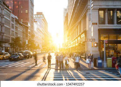 Bright light of sunset shines on crowds of people crossing the busy intersection on 5th Avenue in Manhattan, New York City