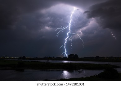 Bright lightning bolt with many side branches strikes down to earth in a river landscape