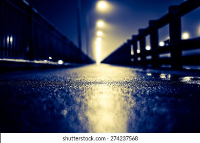 The bright lights of the city at night, walk across the bridge. View from ground level, image in the yellow-blue toning