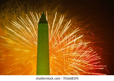 Bright lights from fireworks light up the sky with the Washington Monument in the foreground on the 4th of July celebration. Washington DC., USA