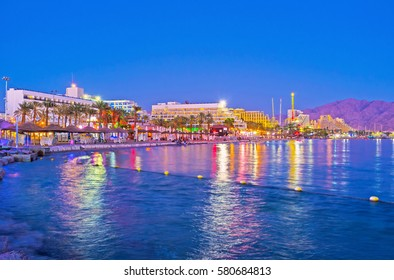 The bright lights of the night city are reflected in waters of the Red Sea, Eilat, Israel.