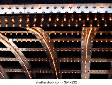 The bright lights of a theatre marquee in a downtown city