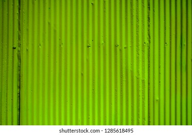 Bright lime green corrugated metal zinc wall for background or texture