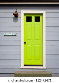 "A bright, lime green door with white wood trim in a light gray wood sided home exterior, including a ""to beach"" arrow sign."