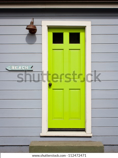 """A bright, lime green door with white wood trim in a light gray wood sided home exterior, including a """"to beach"""" arrow sign."""