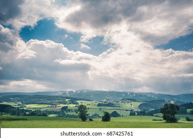 Bright lit clouds above the hills. Steam from the last shower is hanging between the trees of the forrest in the distance