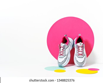Bright lit scene with chunky sneakers and huge confetti. Colorful casual wear or footwear. Minimalist fashion fitness creative concept.