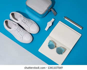 Bright lit white, blue and silver female accessories. Sun glasses, watches, notebook, pencils, sneakers and purse are ordered on a blue and silver asymmetrical paper background.