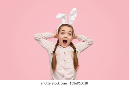 Bright little girl with braids and in bunny ears holding hands on head and screaming at camera in excitement
