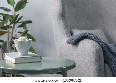 A bright living room with a book and a bowl of prickly pears placed on a green metal side table