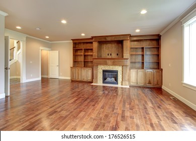 Bright living room with hardwood floor, beige wall, wooden storage combination and stone background fireplace