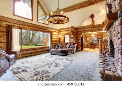 Bright Living room interior in American log cabin house. Rustic chandelier, stone fireplace and high ceiling with wooden beams make room gorgeous. Northwest, USA