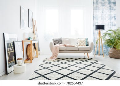 Bright living room interior with beige sofa and wooden lamp standing against the window