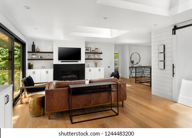 Bright Living Room in New Home, with Hardwood Floors, Fireplace, TV, and Open Concept Floor Plan. Features Large Skylights and White Walls and Cabinets.