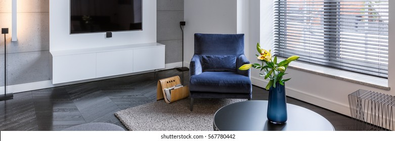 Bright living room with tv, blue armchair and round table, panorama