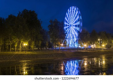 A bright luminous observation wheel against a dark sky on the embankment of the River Uvod in Ivanovo.