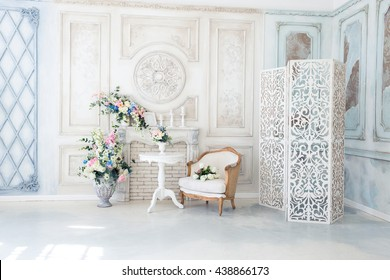 Bright luxury white and blue colored interior living room with flowers in vases. the walls are decorated with baroque ornaments