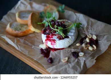 Bright macro photo of beautiful delicious fresh cheese with berries and nuts on the table