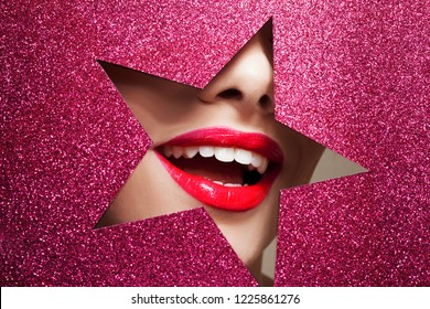 Bright makeup and you're a star. Beautiful girl close up, paper in the shape of a star. smiling young woman red lips and white teeth
