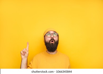 Bright man in yellow sweater and hat looking up and pointing with finger in excitement.