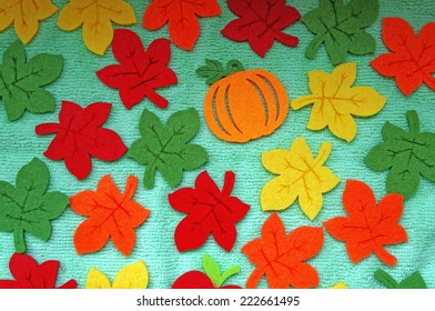 Bright Maple leaves out of felt on a light green fabric as a background
