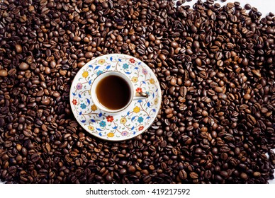 Bright mass of arabica coffee beans and small plate with coffee cup in oriental style. Top view on still-life with coffee.