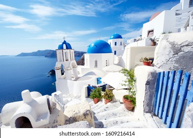 Bright Mediterranean morning scene of Oia Village dominated by a blue gate and matching church domes in Santorini, Greece