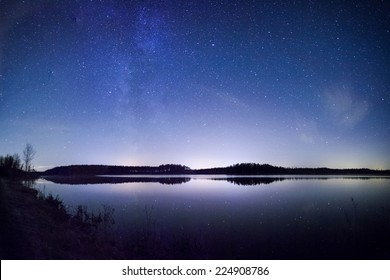 Bright Milky Way over the lake at night in Finland.