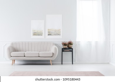 Bright, minimalist living room interior with beige sofa standing near the window and black stool