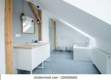 Bright modern bathroom with grey walls, mirror and bathtub. Modern bright flat apartment in the attic