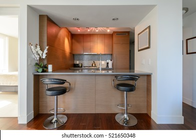 Bright modern kitchen with leather bar stools. Interior design.