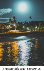 Bright moon reflecting on the ocean water on a beach in Waikiki Oahu Hawaii