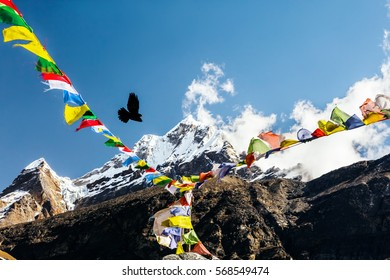 Bright Mountain View from high Altitude Camp of Himalaya Mountaineering Expedition Nepalese colorful Prayer Flags on Foreground