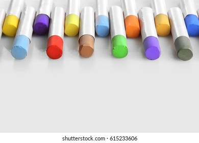 Bright multicolored chalk for drawing lies on a white background
