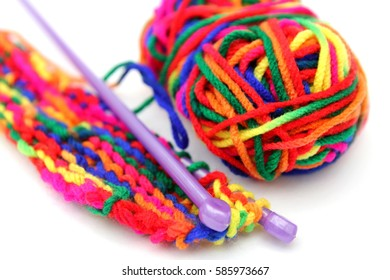 Bright multi-colored colourful knitting wool or yarn with knitting needles on white background