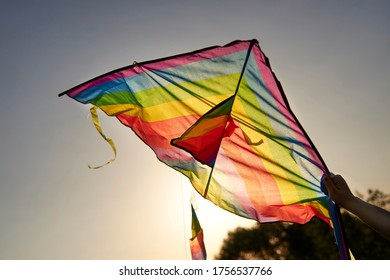 Bright multi-colored kite in a woman's hand against the sky, the theme of summer fun.