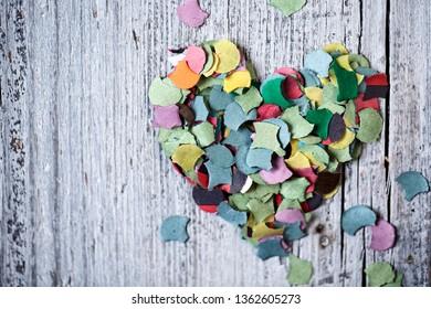 Bright multicolored Paper Confetti on Table in Heart Shape