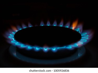 A bright neon blue flame emitting from a cooker hob.