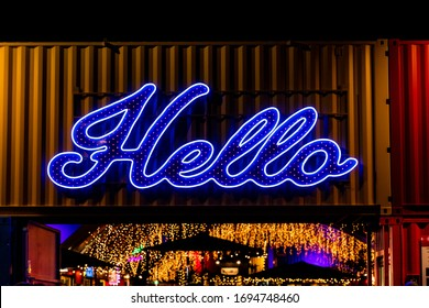 A Bright Neon Hello Sign Above a Doorway Lights up the Entrance to a Busy Building